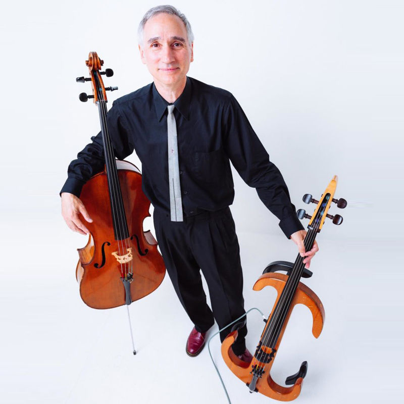 Gideon Freudmann with right arm around an acoustic cello and left hand holding an electric cello.
